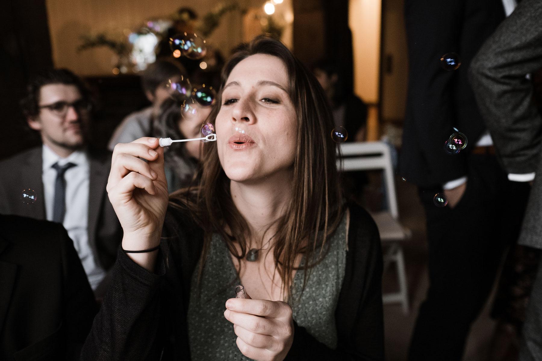 ein Gast des Brautpaar pustet Seifenblasen