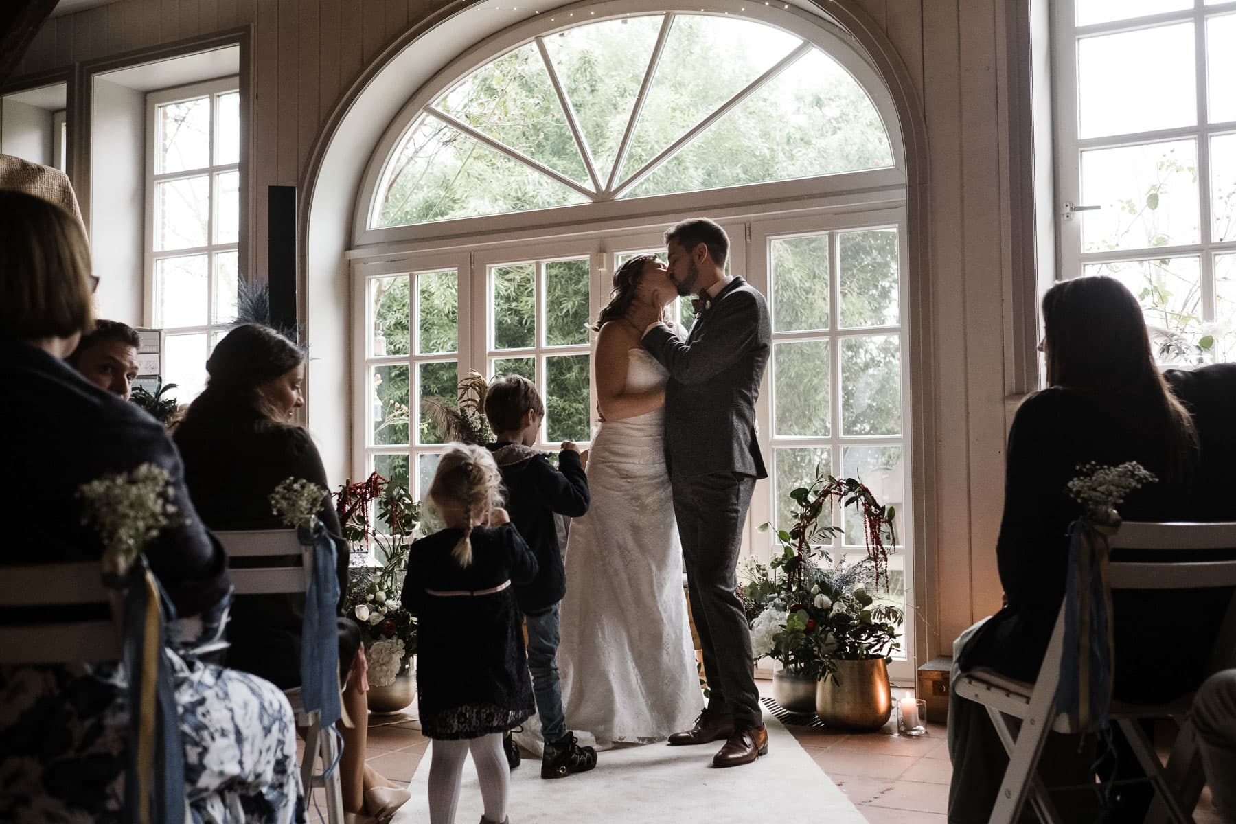 das Brautpar steht vor einer großen, helln Bogentür in einem Trauzimmer in einem Landhaus, sie küssen sich, um sie herum sitzen ihre Gäste auf weißen Holzklappstühlen