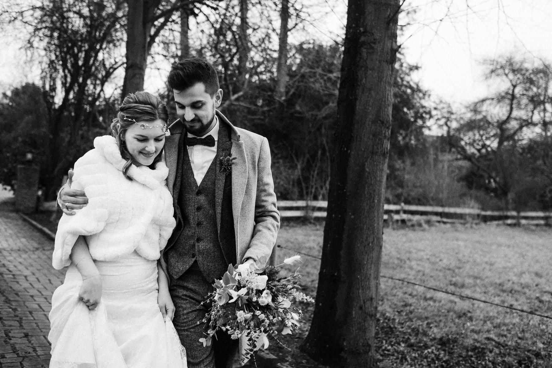 das Brautpaar geht Arm in Arm draußen auf einen Weg, der umgeben von kahlen Bäumen ist, sie schauen beide nach unten, die Frau trägt über ihrem Brautkleid einen weißen Pelzumhang, der Mann trägt über seinen Anzug einen Wollmantel