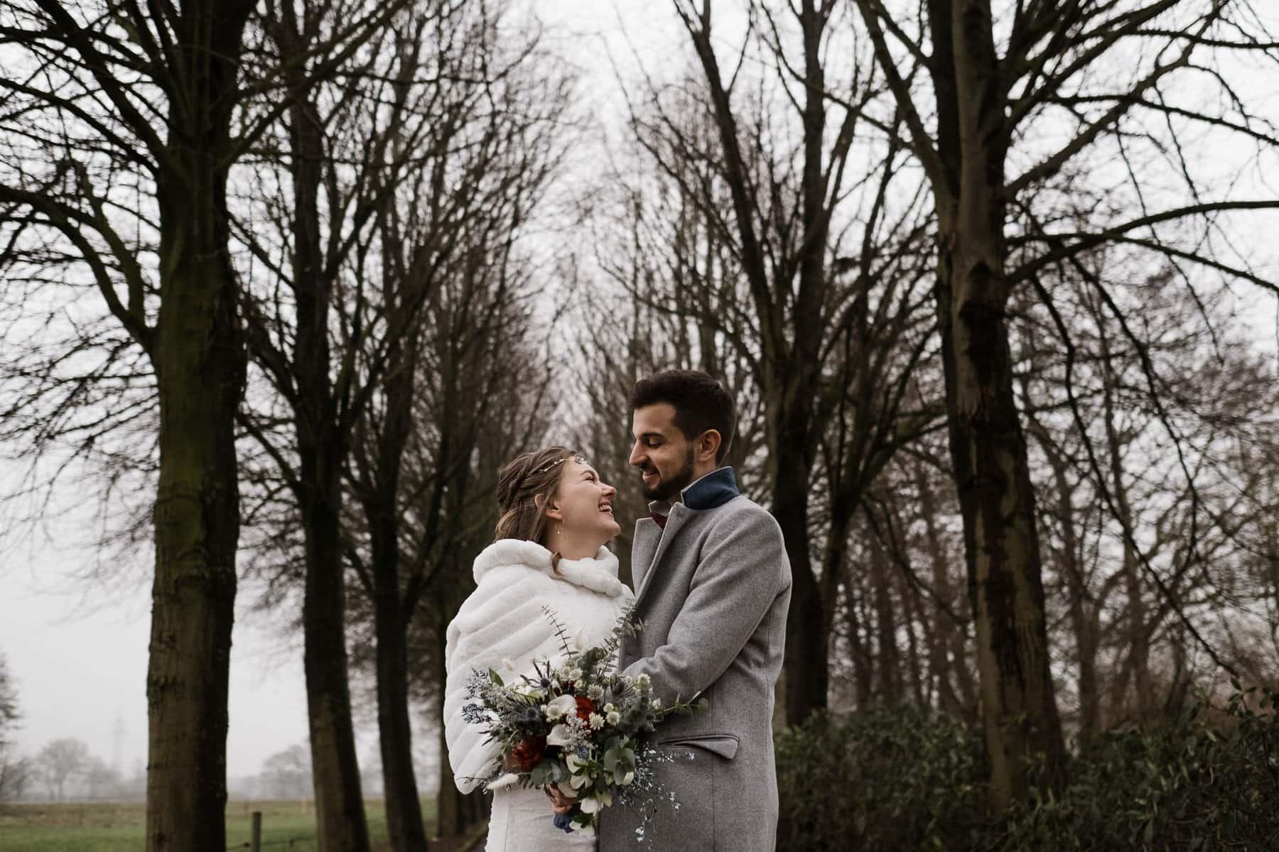 das Brautpaar steht draußen auf einem Weg, am Wegesrand stehen kahle Bäume, der Bräutigm hält die Braut in seinen Arm, sie schauen sich an, die Braut trägt über ihren Brautkleid einen weißen Pelzumhang, der Bräutigm trägt einen grauen Anzug