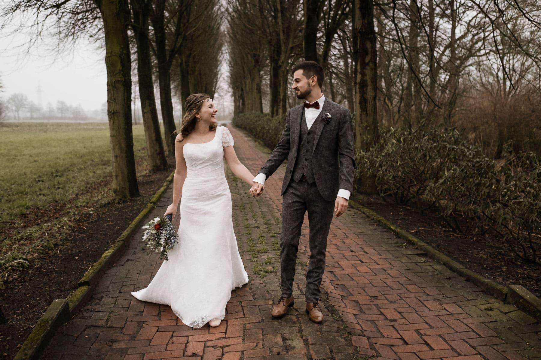 auf einem mit roten Steinen gepflasterten Weg steht das Brutpaar Hand in Hand, am Wegesrand stehen einige kahle Bäume, sie schauen sich an, sie trägt ein weißes Brutkleid und einen üppigen Blumenstrauß in der Hand, er trägt einen grauen Anzug