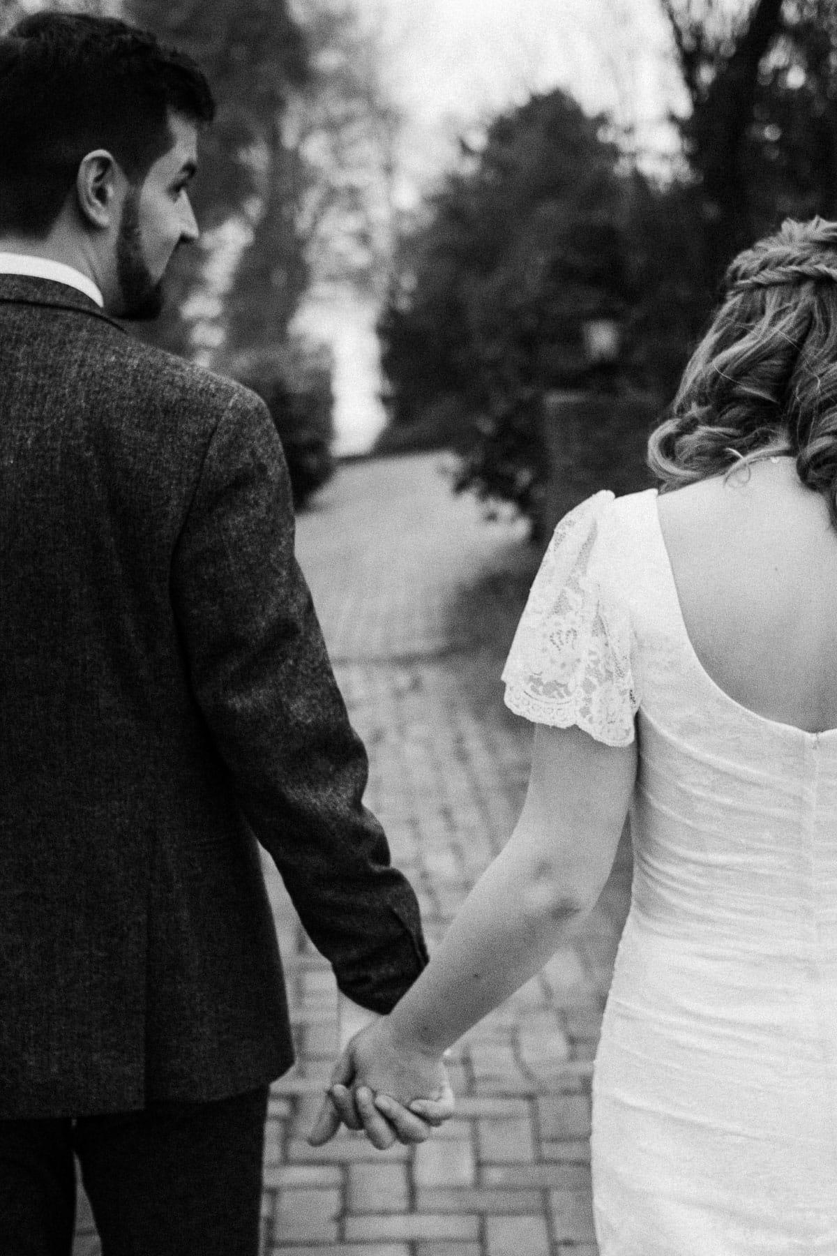 das Brautpaar geht Hand in Hand einen kleinen, gepflsterten Weg eines Gartens entlang, sie trägt ein langes Brautkleid, er trägt einen Anzug