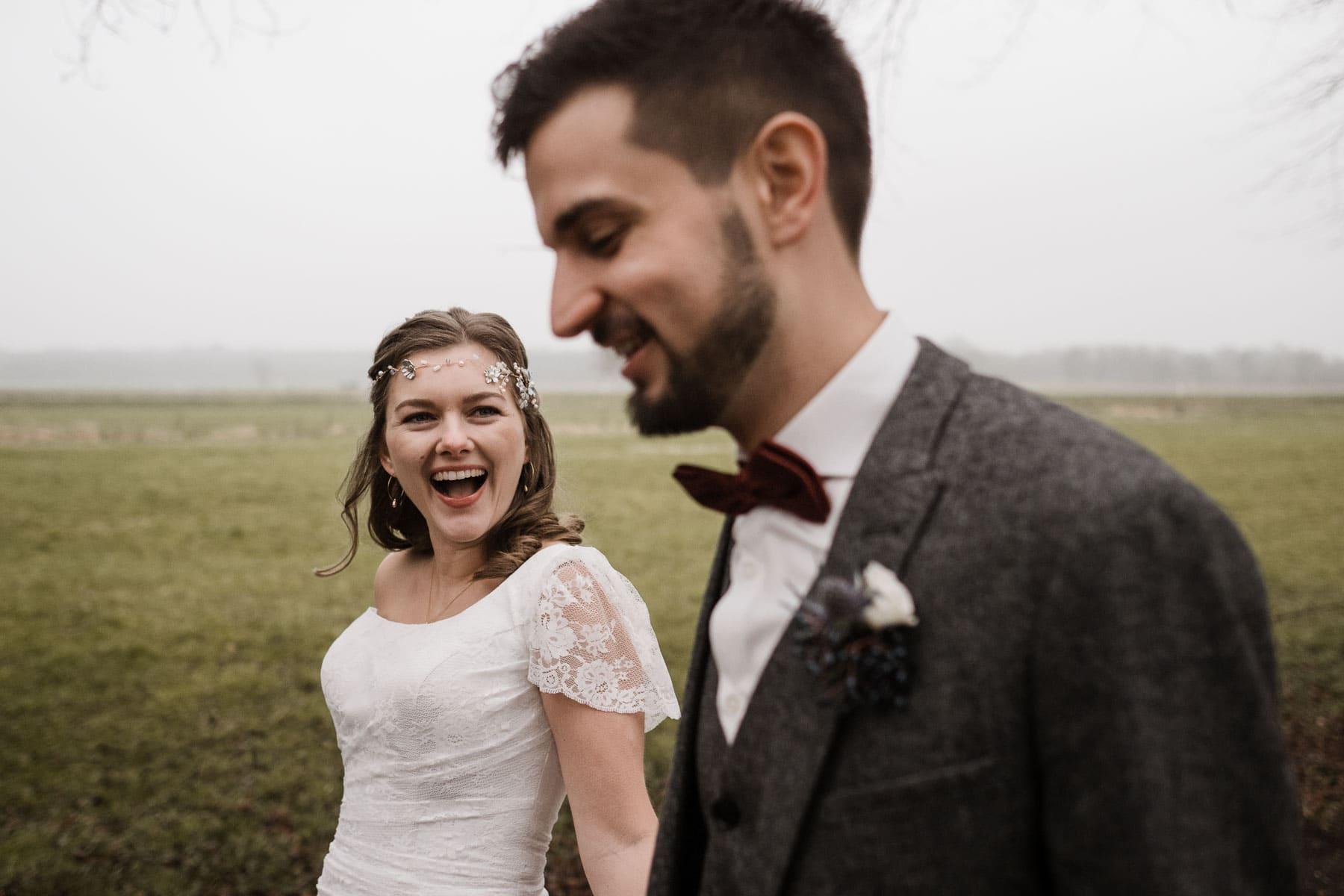 ein Brautpaar steht draußen vor einer großen Weide, in der Ferne ist es nebelig, das Brautpaar steht nebeneinander, Hand in Hand, die Braut schaut zu dem Bräutigam, sie lacht