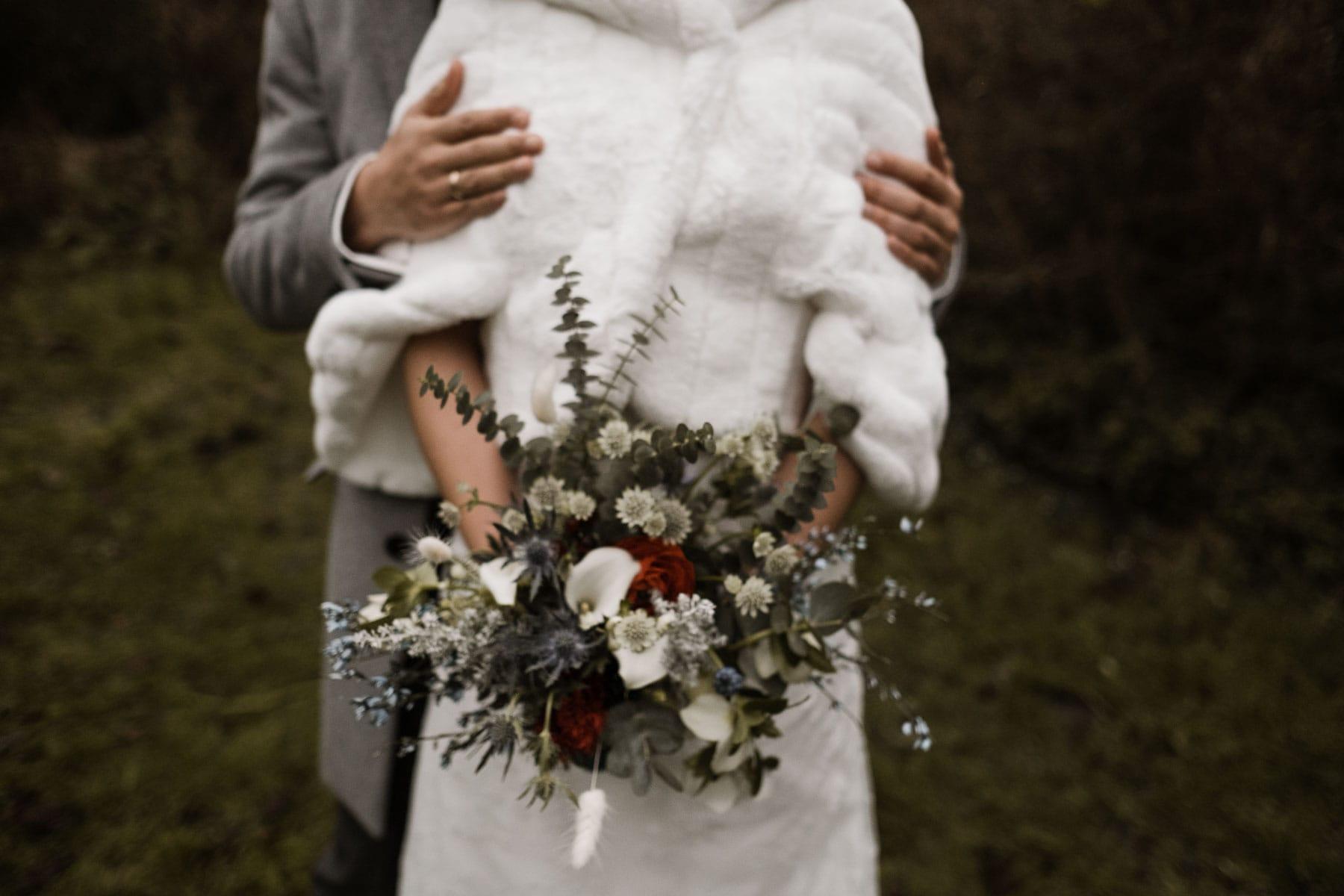die Braut trägt in weißes, langes Brautkleid und darüber einen weißen Pelzumhang, sie hält in den Händen einen großen Blumenstrauß, der Mann steht hinter ihr und hält seine Hände an ihre Oberarme