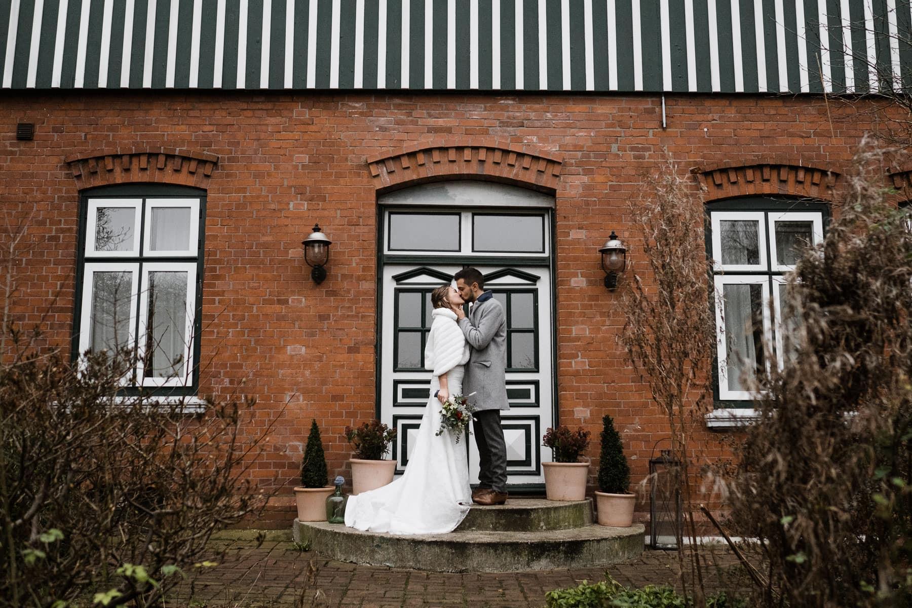das Brautpaar steht vor der Holztür eines Landhauses, es hat große, helle Sprossenfesnster aus Holz, die Braut trägt ein langes Brautkleid mit einem weißen Pelzumhang, der Mann trägt über seinen Anzug einen Wollmantel, das Brautpaar küsst sich