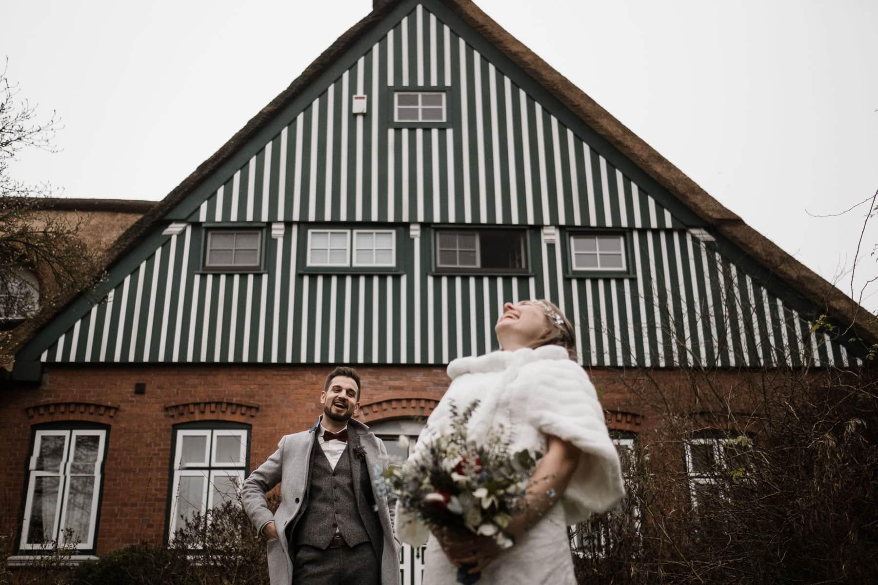 vor einem Landhaus steht ein Brautpaar, der Giebel des Hauses ist mit weißen und grünen Holtbrettern vertäflt, das Haus hat Sprossenfenster aus Holz, die Braut trägt ein langes Brautkleid mit einem Pelzumhang, sowie einen großen Blumenstrauß in der Hand, der Bräutigam trägt über seinen Anzug einen Wollmantel, die Braut legt ihren Kopf in den Nacken und lacht dabei, der Bräutigam schaut auf die Braut