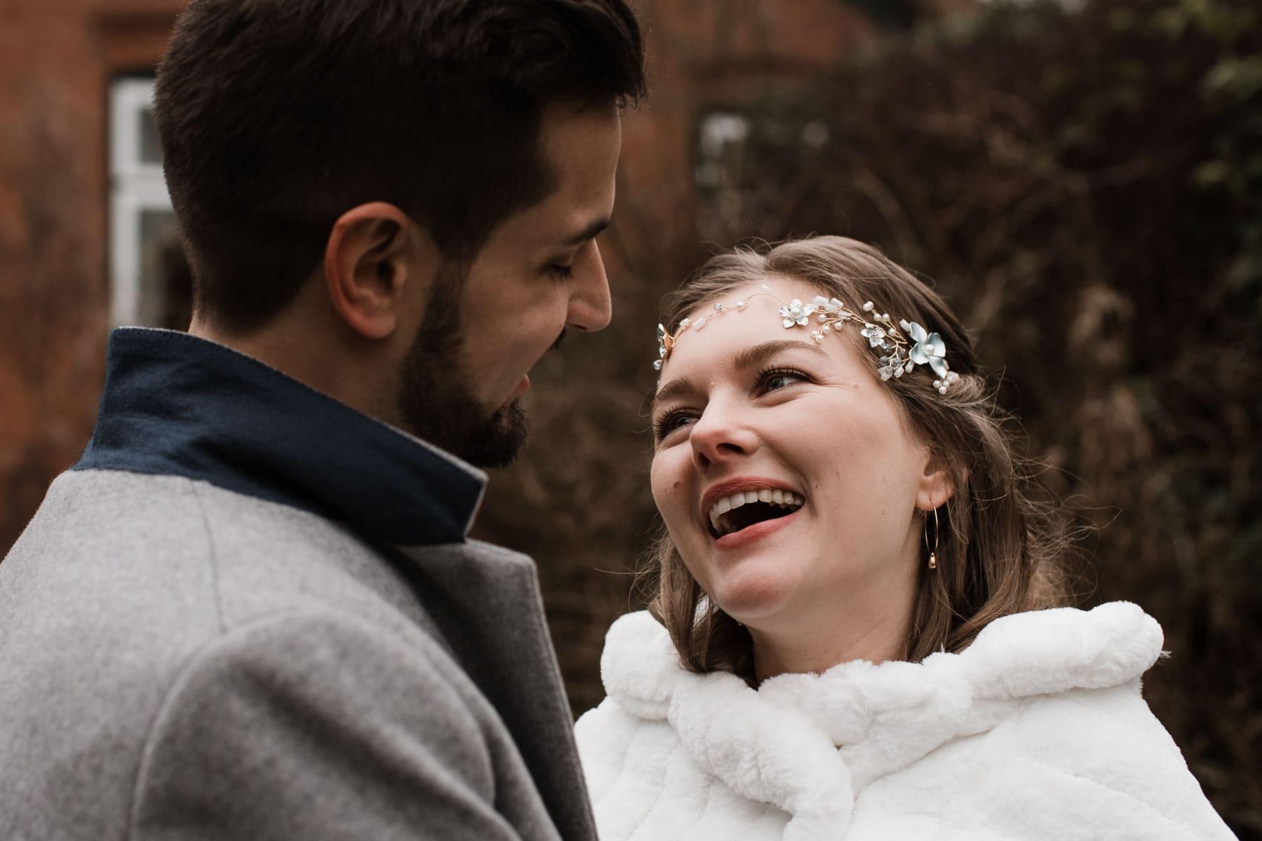 die Braut und der Bräutigam stehen draußen, die Braut trät über ihrem Brautkleid einen weißen Pelzumhang und einen Stirnreif, der Mann trägt über seinen Anzug einen Wollmantel, die Braut schaut dem Bräutigam ins Gesicht und lacht dabei