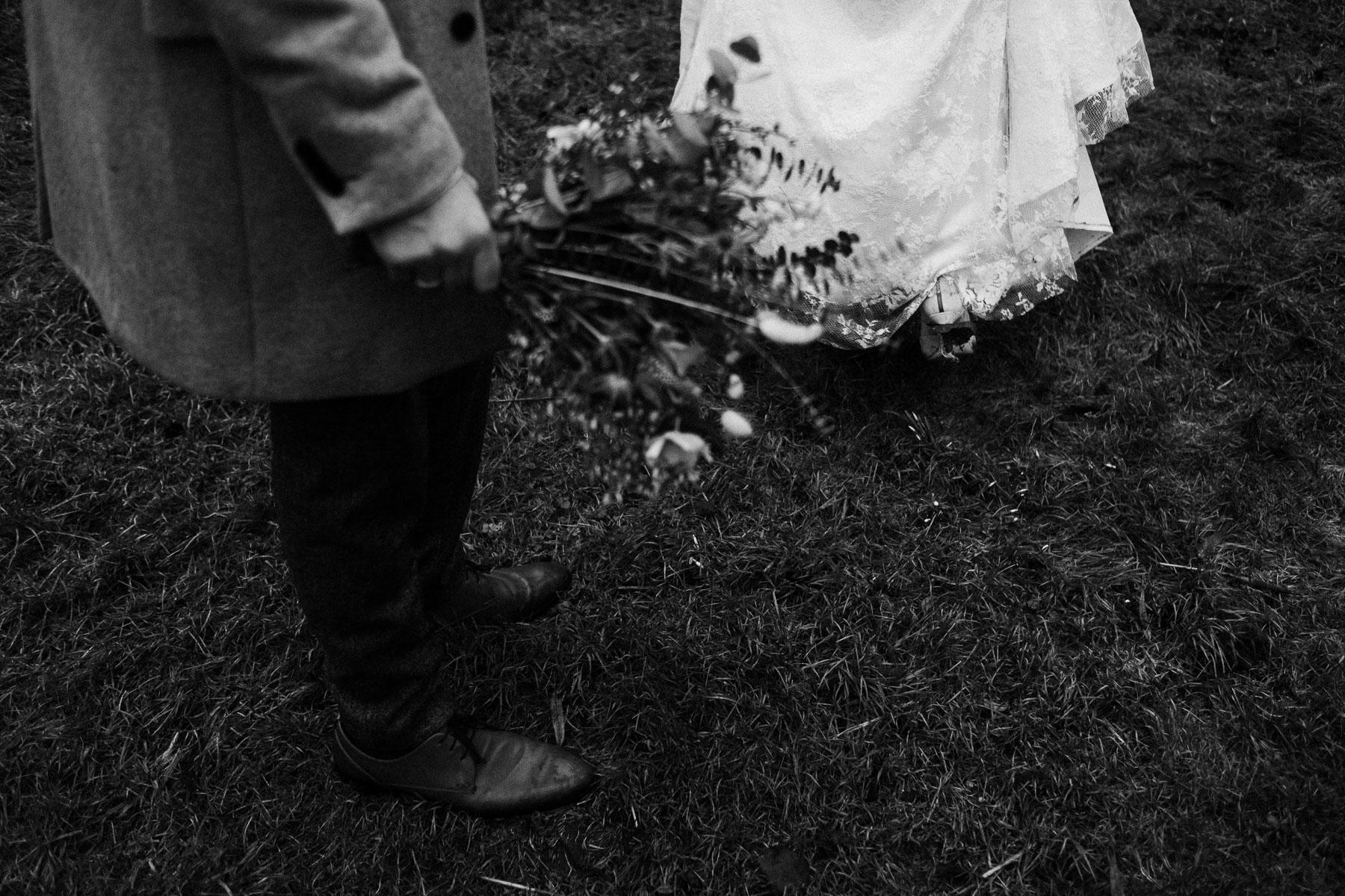 das Brautpaar steht auf dem Rasen, zu sehen sind nur die Beine, der Mann trägt einen gruen Anzug und die Braut ein langes Brautkleid, der Mann hält den großen Brautstrauß
