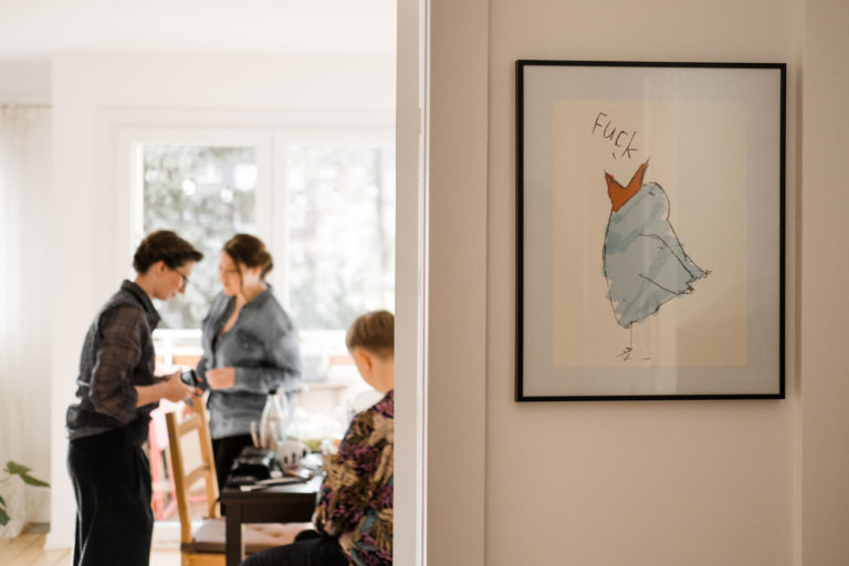 Im Vordergrund ein Bild an der Wand hängend, im Hintergrund unscharf dargestellt, das Brautpaar beim Gettting Ready.