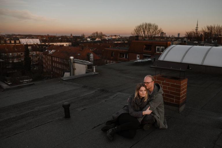 Paarogtografie Hamburg- Bilder im Sonnenuntergang über den Dächern Hamburgs. Sitzend ineinander gekuschelt auf dem Dach.