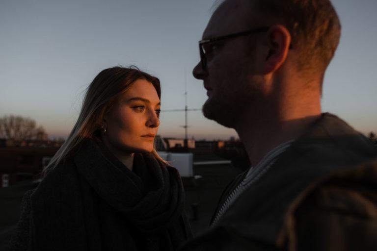 Paarogtografie Hamburg- Bilder im Sonnenuntergang über den Dächern Hamburgs. Sonne streift die Gesichter der beiden.
