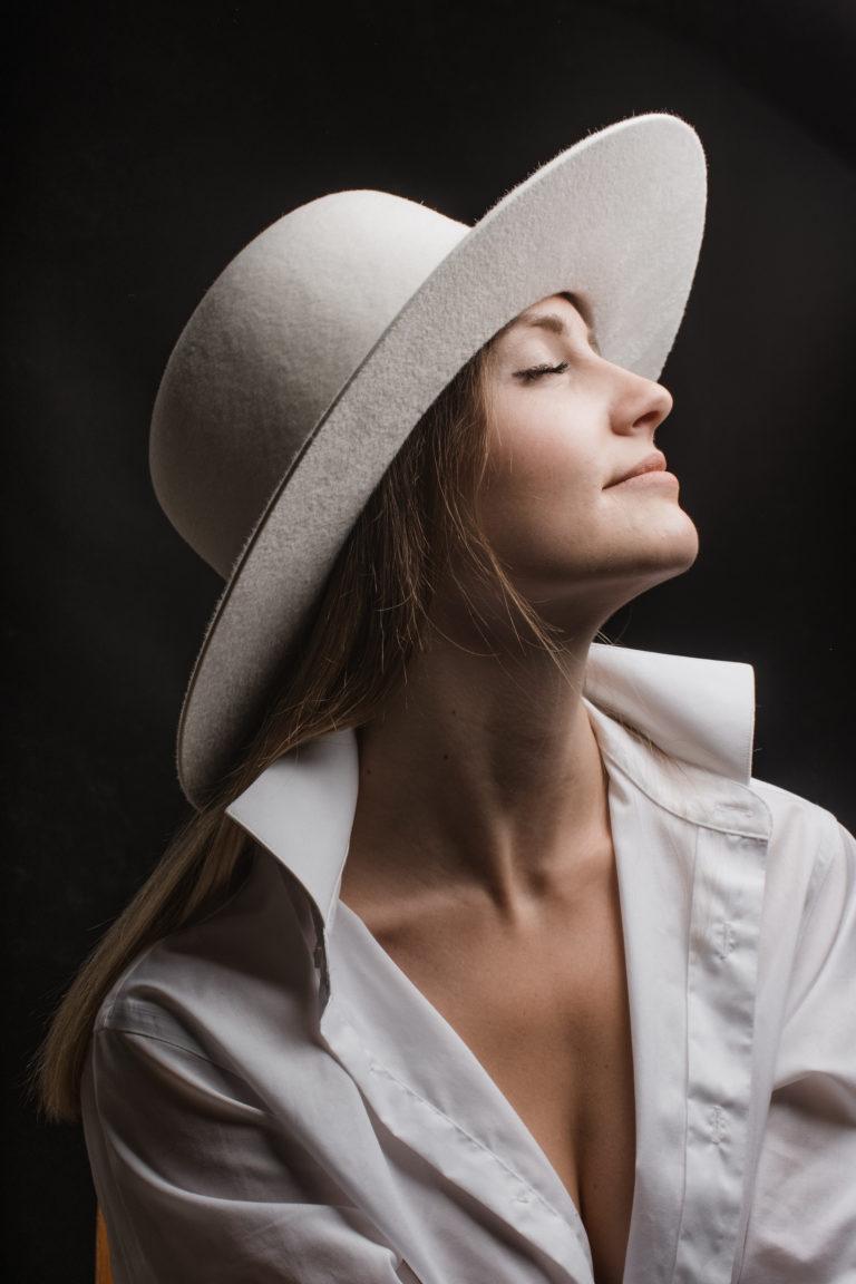 Editorial- Rotkäppchen Design- Portrait Hutmanufaktur- weißer Hut Model Das Gesicht in Richtung Licht gewendet.