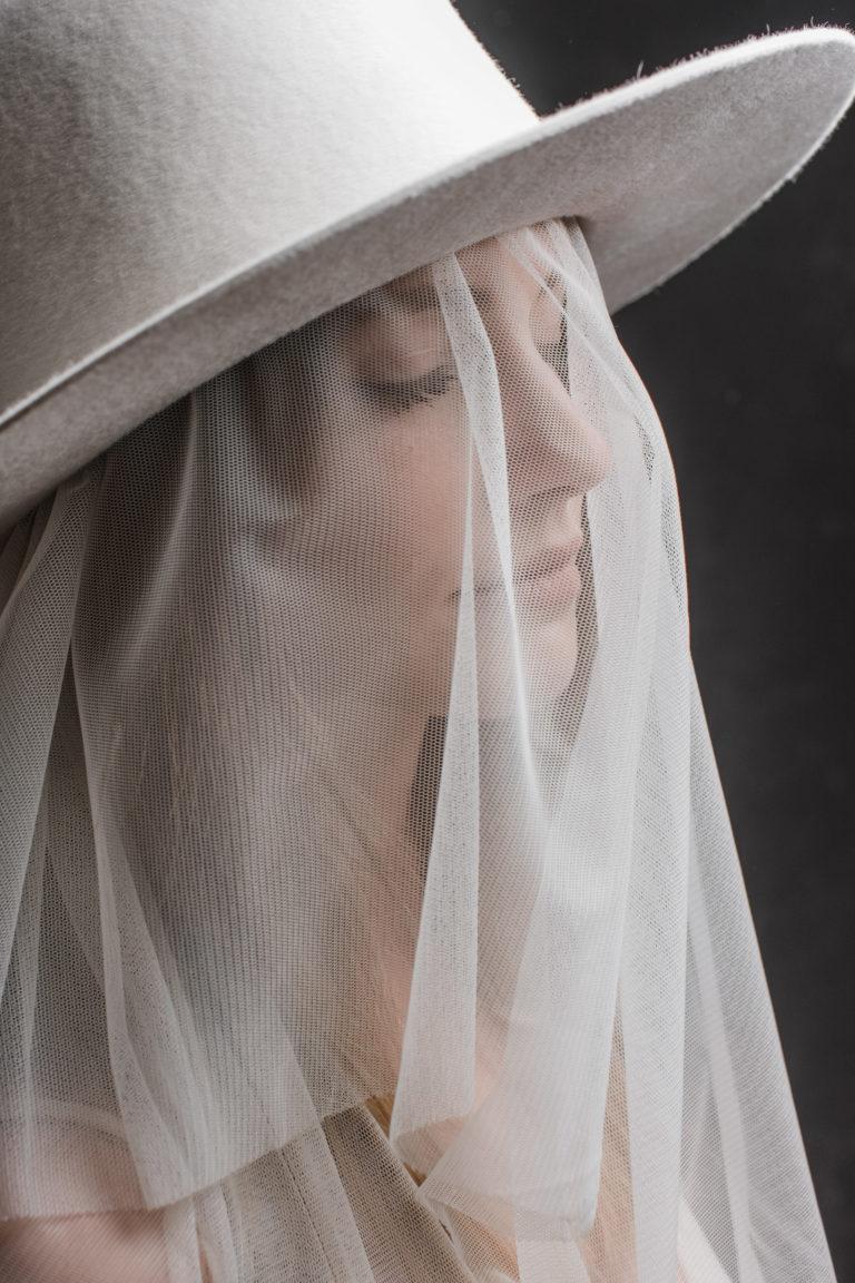 Editorial- Rotkäppchen Design- Portrait Hutmanufaktur- weißer Hut mit Schleier_Model mit geschlossenen Augen.