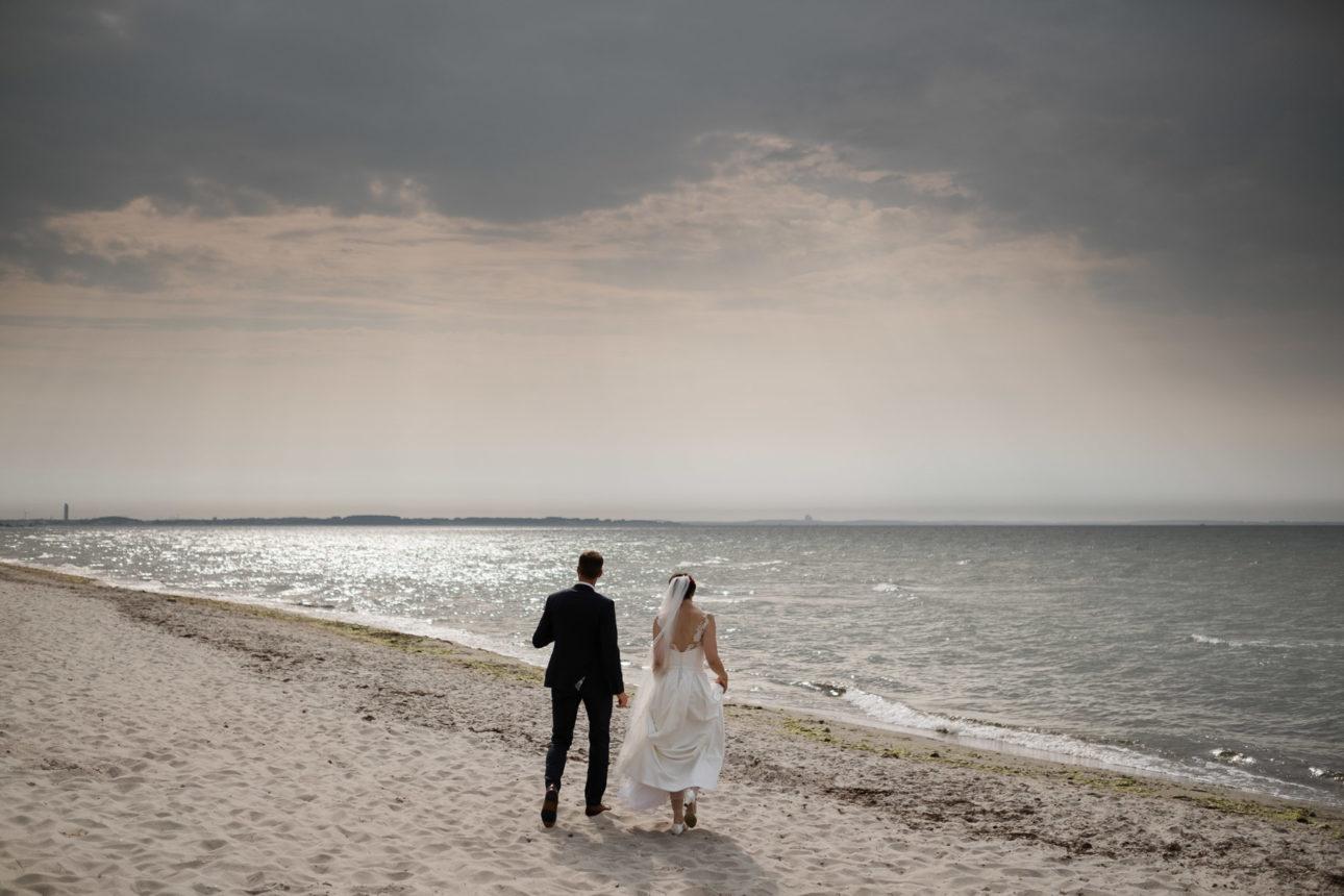 Schlossgut-Groß-Schwansee- Hochzeitsfotografie- Hochzeitsbilder an der Ostsee- Hochzeitspaar geht auf die See zu. Über ihnen ein dramatischer Himmel.