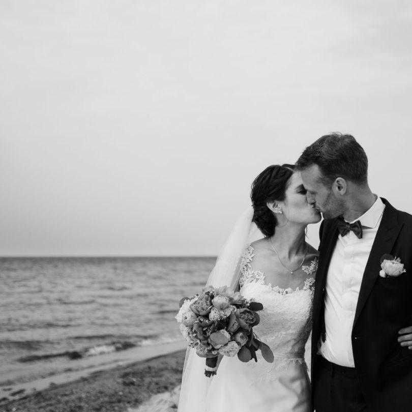 Schlossgut-Groß-Schwansee- Hochzeitsfotografie- Hochzeitsbilder na der Ostsee- Hochzeitspaar geht Arm in Arm die See entlang