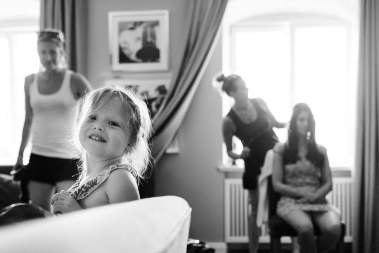 Hochzeitsfotografie-Schlossgut-Groß-Schwansee- Getting Ready Braut- Kind der Trauzeugin schaut frech in die Kamera.