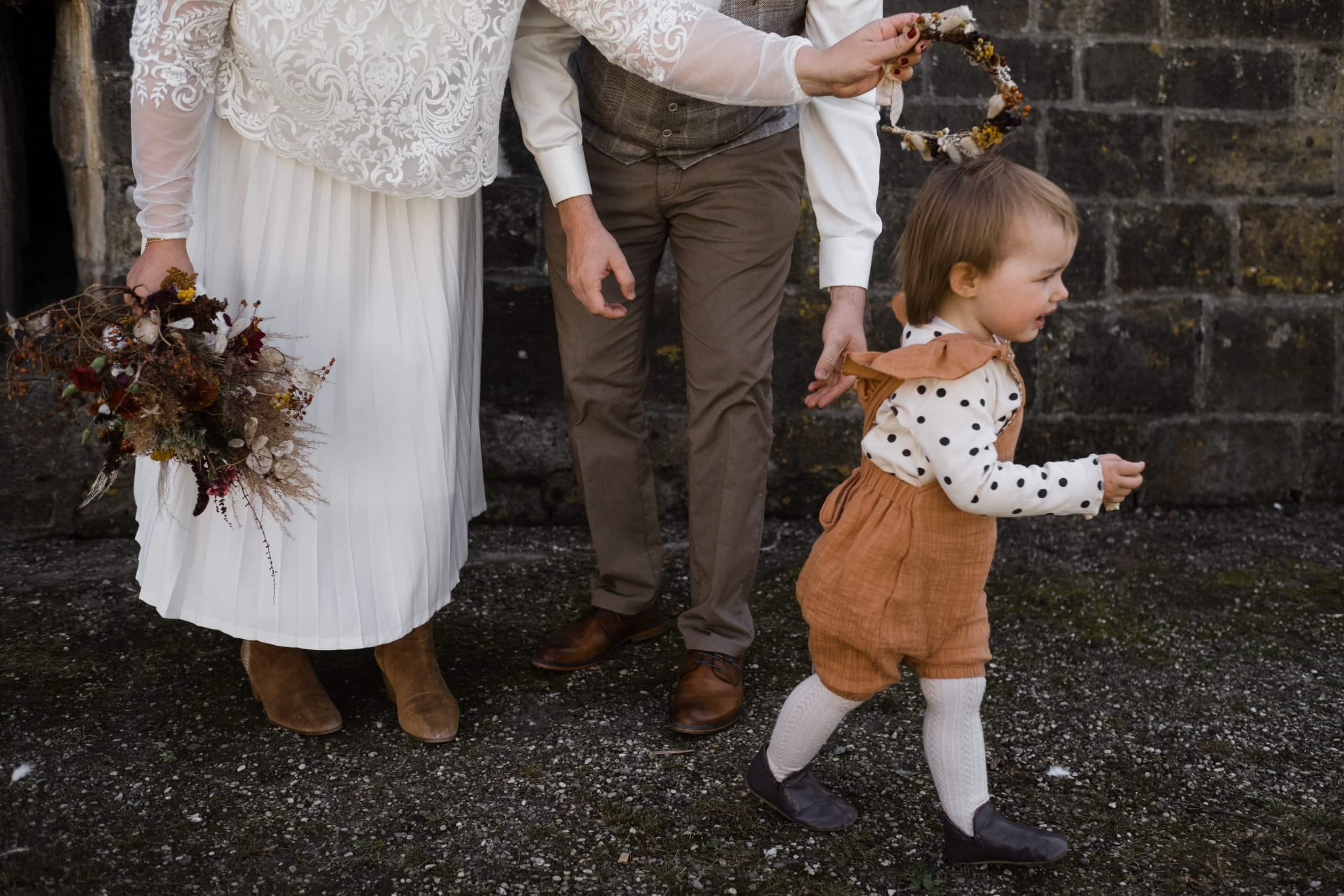 Hochzeitsfotografie-Hamburg- Hochzeitsbilder Hamburg- Kind flüchtet vor dem offiziellen Hochzeitsfoto mit den Brautpaar.
