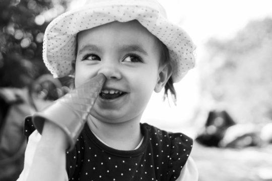 Hinweis auf die Familienfotografie von Frau-Siemers, Es ist ein Kind zu sehen, das mit einem Sandspielzeug in der Nase popelt.