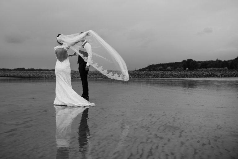Hochzeitsfotografie Elbstrand Hamburg- After Wedding Session- Schleier der Braut weht im Wind.