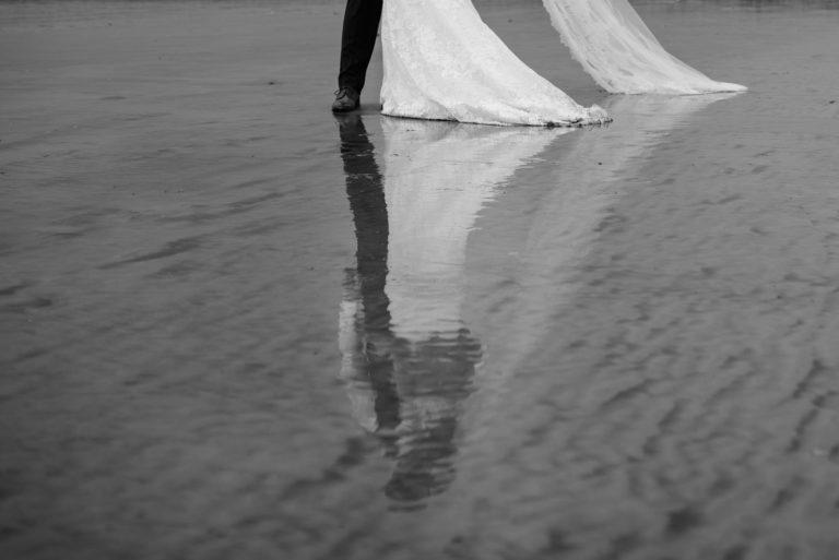 Hochzeitsfotografie Hamburg- After Wedding Session Elbstrand- Hochzeitspaar spiegelt sich im Wasser der Elbe.