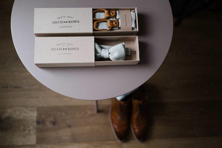 Hochzeitsfotografie Kieler Kaufmann- Getting Ready Bräutigam- Detailaufnahme Adam Bows- Fliege und Hosenträger