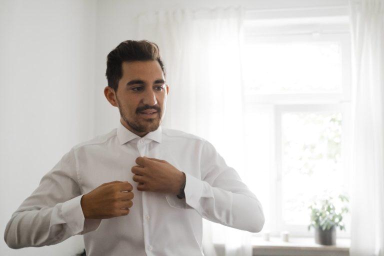 Getting Ready zu Hause- der Bräutigam knöpft sein Hemd zu.