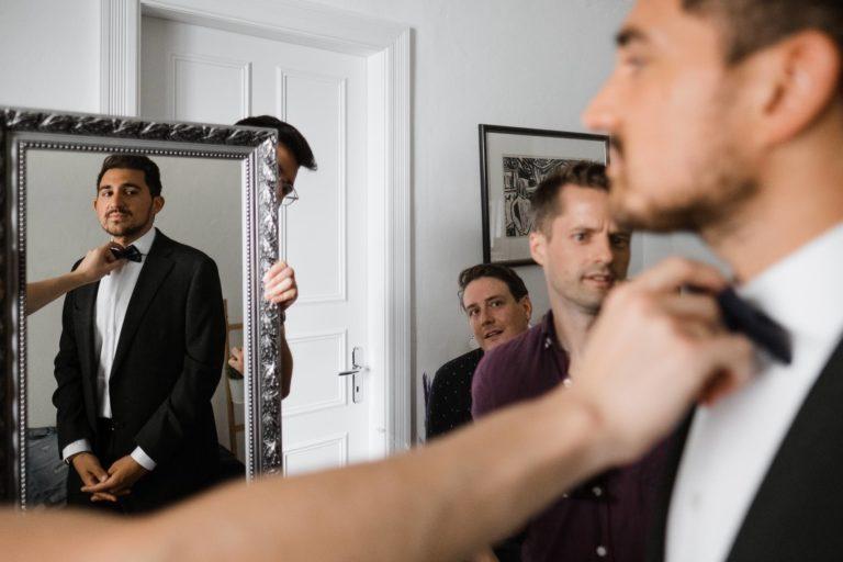 Hochzeitsfotograf Hamburg- Hochzeitsreportage- Getting Ready zu Hause- Der Trauzeuge kontrolliert die Fliege des Bräutigams.